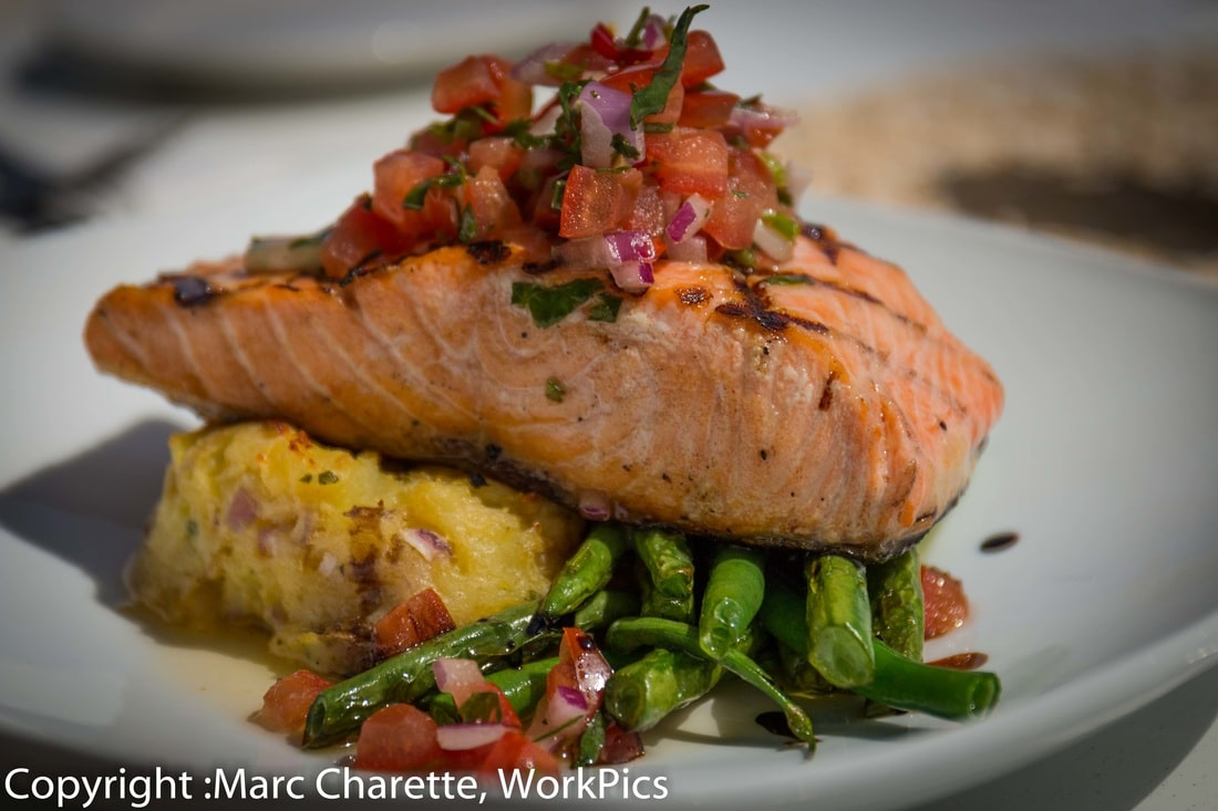 Commercial food photography of plated salmon in waterfront restaurant