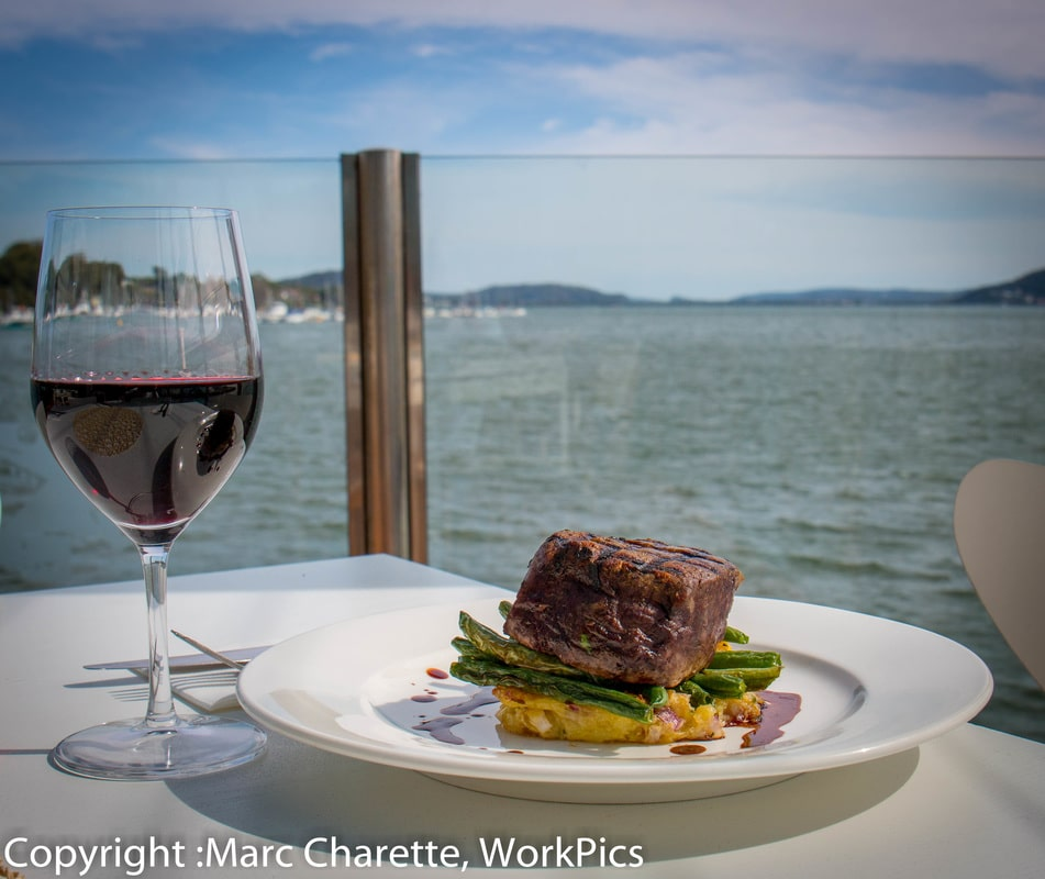 Commercial photography of beer and wine with a view at waterfront restaurant