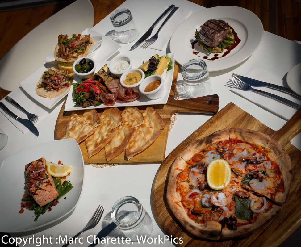 Commercial photography of restaurant table with various meals served and antipasto share platter