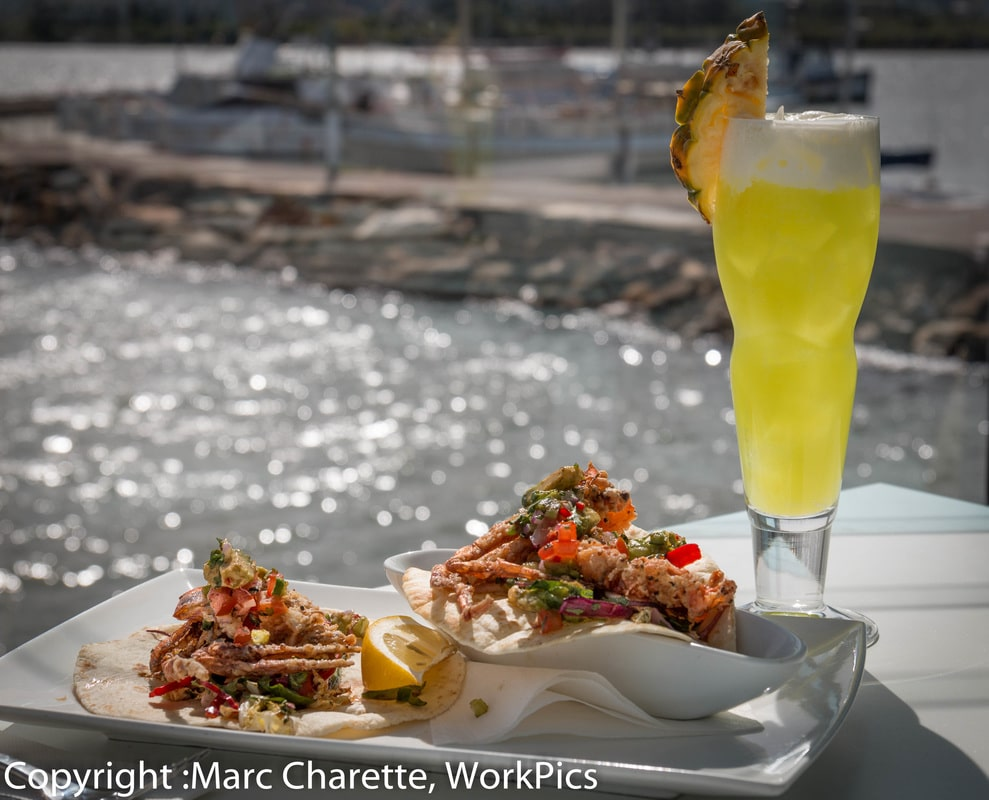 Commercial photography of waterfront restaurant with plated seafood and cocktail and water views