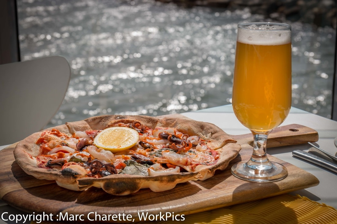 Commercial photography of waterfront restaurant with seafood pizza and beer on table